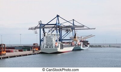 Cranes and reachstackers load few vessels in port with windmills in sea near coast