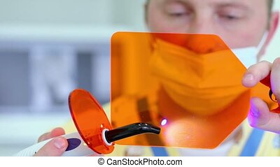 Doctor in mask hold orange glass and illuminates spots on it