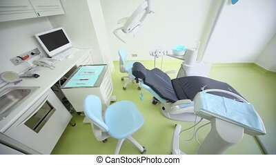 Dental surgery with tv set above chair and other equipment,...