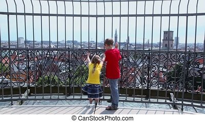 Two kids hang on lattice with cityscape beyond - Two kids...