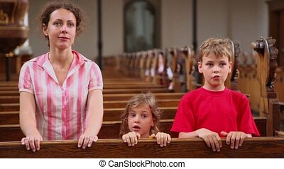 Mother with two her kids stand near bench in cathedral