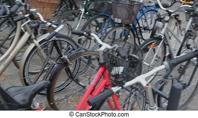 Many bicycles with baskets on parking, closeup view in motion