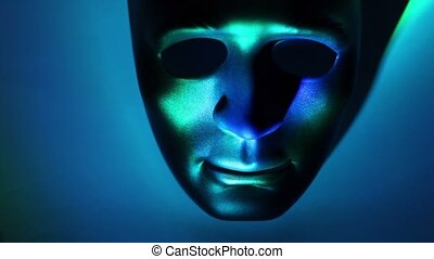 Black theatrical mask lit by color light which changes