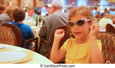 girl behind table at restaurant wearing spectacles - girl...
