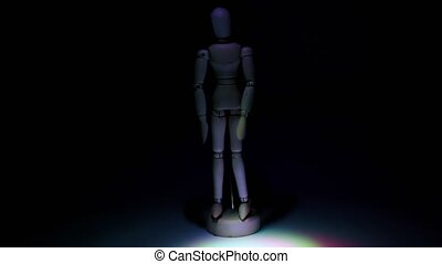 Wooden toy men lit by color light at dark background