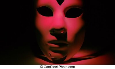 White theatrical mask lit by color light which changes at...