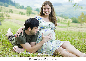 Pregnant couple - Husband with pregnant wife is resting in...