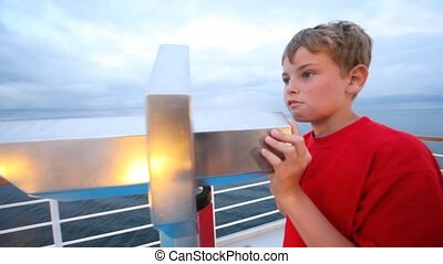 boy looks in stationary field-glass afar from ship deck close up
