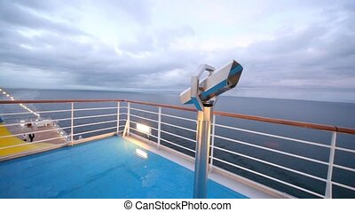 empty main deck with viewing field-glasses and sea in distance