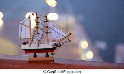 modeling ship with sails and Norway flag stands on handrail...