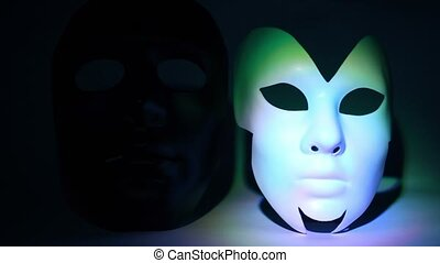 Two theatrical masks black and white lit by light at dark...