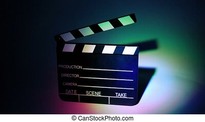 Film slapstick with some information on it in color illumination at dark background