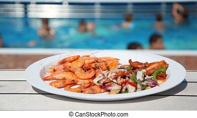plate with seafood, and behind not in focus pool with people...