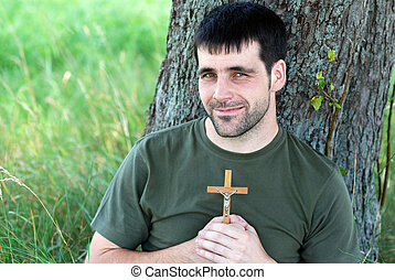 Man with cross is praying under tree