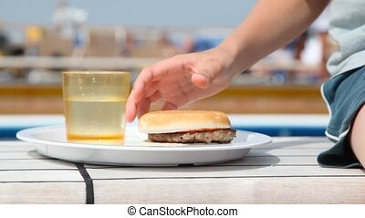 plate with juice and hamburger and hand taking its putting...