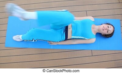 woman in blue lies on rug and does exercise of bending of...
