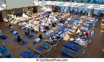 people lie in hall on deck of ship and together do exercises...