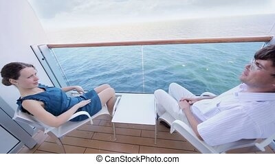 woman and man sit fenced part of deck of ship look at water...