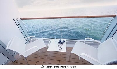 fenced balcony of deck of ship for two with chairs and table