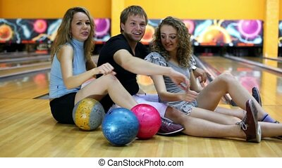 Boy and girls sit and simulate rowing on floor in bowling...