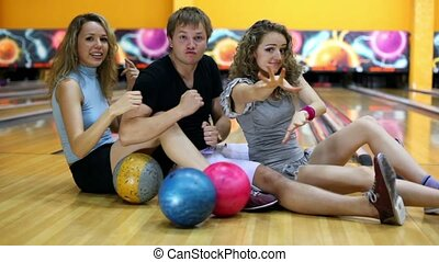Two girls with one guy sit on floor and dance at bowling...