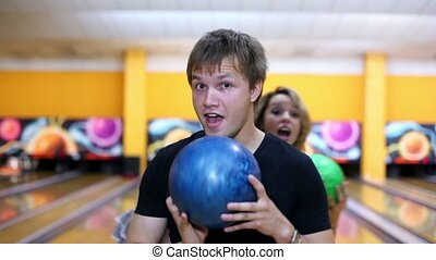 Two girls stand behind boy and they dance with bowling balls