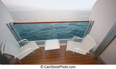 empty balcony of cabin of ship overlooking sea, chairs and...