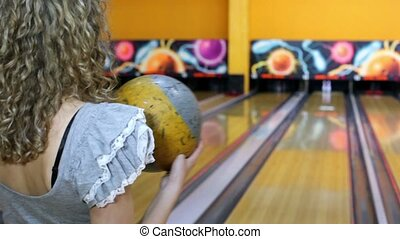 Girl throws bowling ball to beat skittles, and then jumps