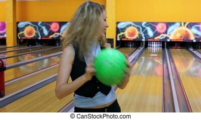 Girl throws green bowling ball to beat skittles, and then jumps very happy with result