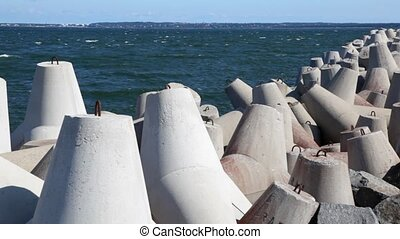 number of concrete waterbreak and stones heap piled on seashore