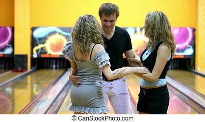 Two girls with one guy dance close to each other in bowling...