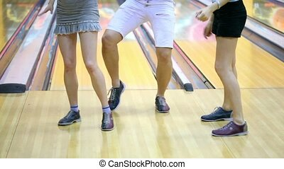 Legs of two girls and one guy dance in bowling shoes