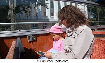 mother in tourist bus tells to daughter something, at which...