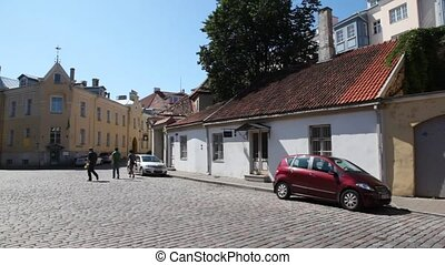 paved stone of street of old city with cars and people