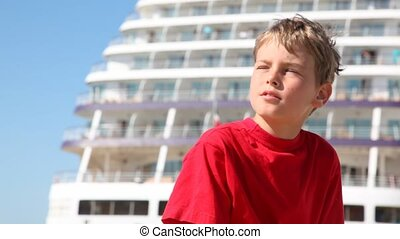 boy squints from sun against decks of big ship close up -...