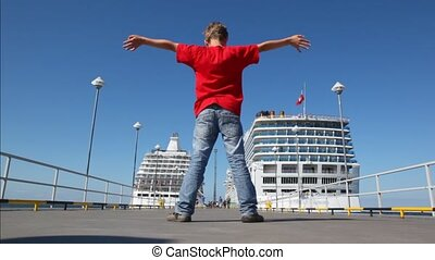 boy is turned having stretched hands on mooring at which...