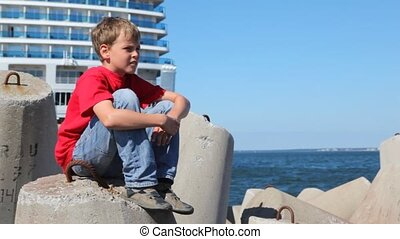 boy sits on concrete breakwater against white liner - boy in...