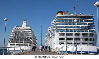 two passenger liners on mooring and people going on it - two...
