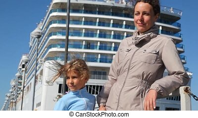 mother and daughter stand alongside against passenger liner,...