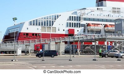 automobile cars go in on ramp on big cargo ship in port -...