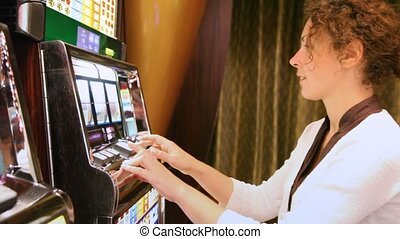 woman presses buttons on slot machine and rejoices to prize