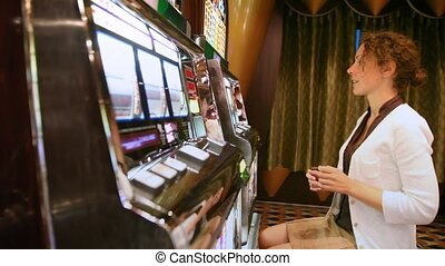 woman plays with slot machine and discontentedly poses face