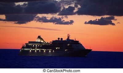Vessel with illumination floats in sea at sunset on cloudy...