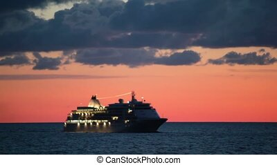Cruise ship with illumination floats in sea at sunrise on...