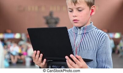 Little boy hold netbook when sits at train station