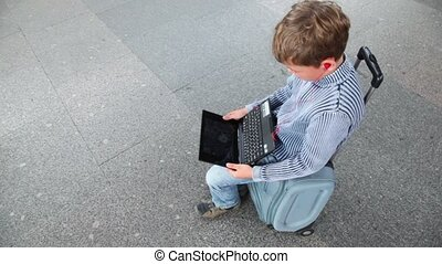 Little boy hold netbook when sits on travelling bag