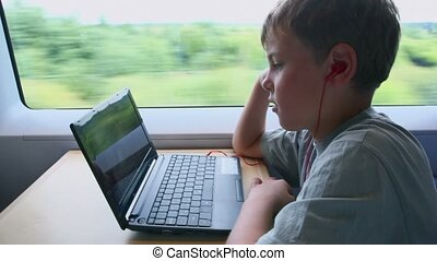 Little boy watch on netbook when sits at train near window