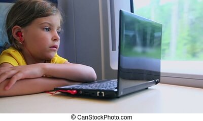 Little girl watch on netbook when sits at train near window