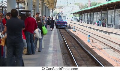 Many people wait for train on platform of railroad station...