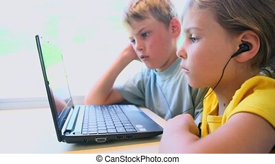 Two kids watch on netbook when sits at train near window -...
